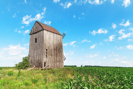 Old wooden windmill in the summer corn field against the blue sky
