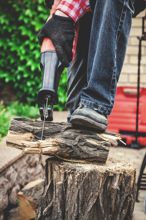 man in a red plaid shirt reciprocating power saw sawing a log. The foot in the shoe presses the log to the stump. Stock Photo