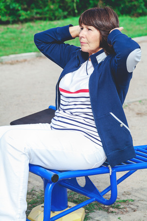Cute active elderly woman carries out exercise on outdoor fitness playground