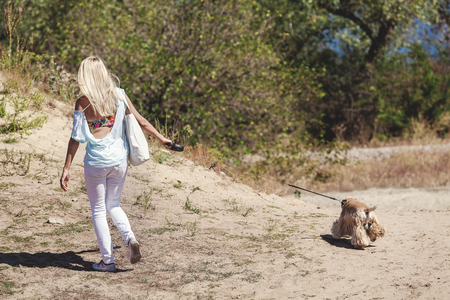 medium size: Girl with her hair is a dog on a sandy slope Stock Photo