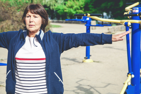 cute active elderly woman performs physical exercises on a street sports field. Stock Photo