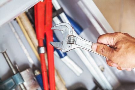 retractable: Hand holding adjustable wrench over a metal box with a variety of locksmith tools closeup