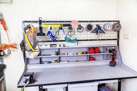Gray metallic metalwork workbench with a set of different tools in the corner workshop