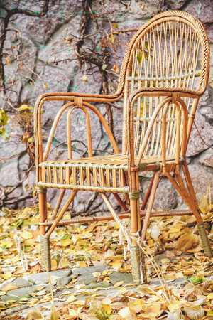 Autumn motive. Beautiful chair woven rattan standing in front of a stone fence in autumn garden Stock Photo