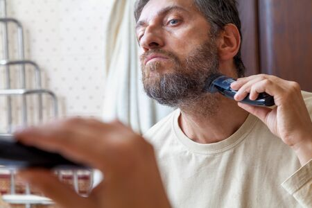 adult sex: Grooming a beard trimmer. A nice gentleman in a beige T-shirt yourself shear his gray beard with the help of machines before a large mirror in the bathroom