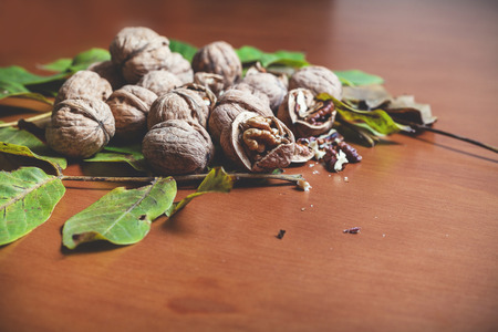 solid background: Group of ripe walnuts and green leaves of the tree lie on a brown background. In the foreground are peeled kernels