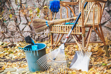 rake, broom and other equipment for the cleaning of fallen leaves is located in front of a beautiful wicker chair in the autumn park