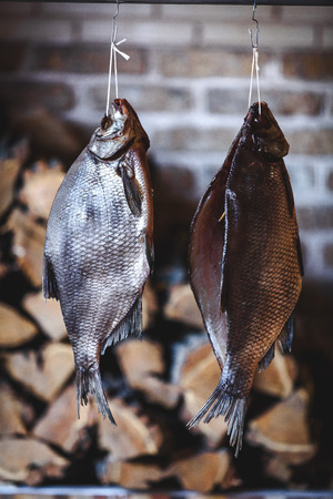 hung: Two large smoked breams are hung on a wooden counter against a brick wall. Firewood is stacked neatly behind