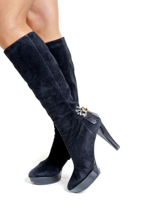 knee boots: Shapely female legs in fashionable high black suede boots with heels. Side view on a white background
