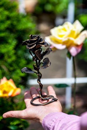 living and non-living. Hand holds graceful wrought-iron rose on a stand. In the background, a real yellow rose