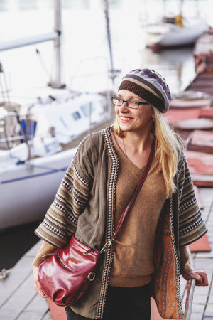 loose hair: Stylish girl with long hair wearing glasses and take stands on the quay for yachts