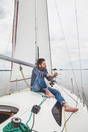 Rest on the yacht. A barefooted man in a striped sweater and jeans sits on the deck of a white yacht under a triangular sail overcast Stock Photo