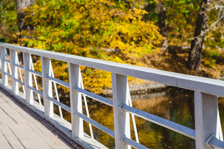 Wooden foot bridge with metal railings over the river a bright autumn day  Stock Photo