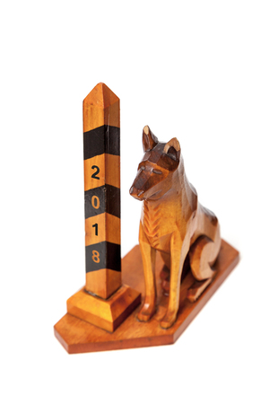 chinese astrology: Symbol 2018. A border dog sits next to a striped pillar. Vintage souvenir from a tree close-up. View from above  Stock Photo