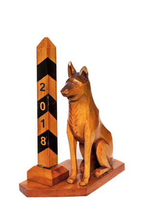 chinese astrology: Symbol 2018. A border dog sits next to a striped pillar. Vintage souvenir from a tree close up