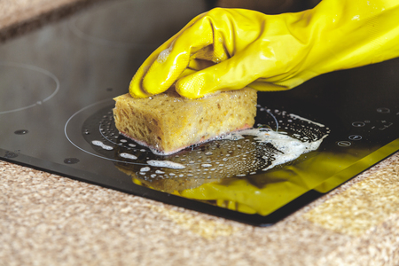 Hands in yellow rubber gloves wash the glass surface of the electric stove with a soft yellow sponge. Is visible soap foam