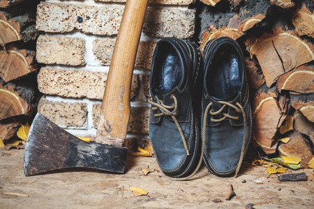 two old boots of the lumberjack are standing vertically on the chopped firewood close-up. Near the big ax Stock Photo