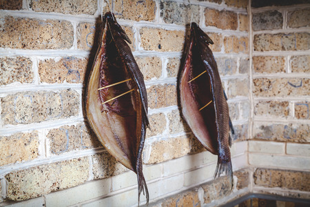 Two large split smoked breams hang on a brick wall