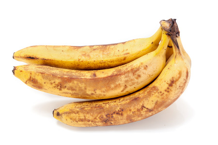 chinese astrology: bunch of ripe bananas lay on a white background. Brown spots on the skin  Stock Photo