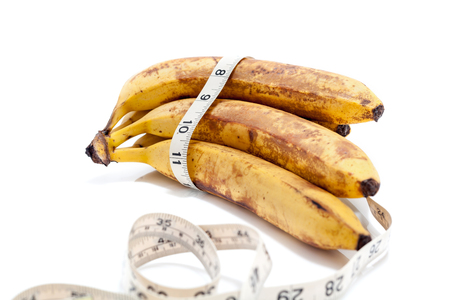 bunch of ripe bananas lay on a white background. Around the banana wrapped centimeter.