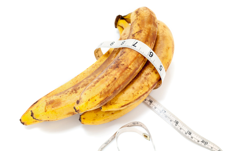 banana skin: bunch of ripe bananas lay on a white background. Around the banana wrapped centimeter.