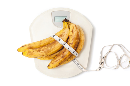 banana skin: bunch of ripe bananas lay on plastic scales. Around the banana wrapped centimeter