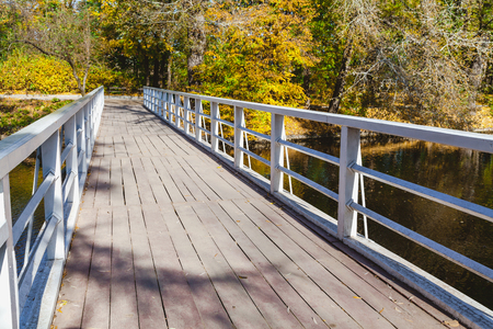 明るい秋の日の川の上の金属製の手すりを木製歩道橋