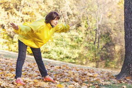 Schöne ältere Frau in einem gelben Blazer in Gymnastik im Herbst Wald, sonnigen Tag beschäftigt Standard-Bild
