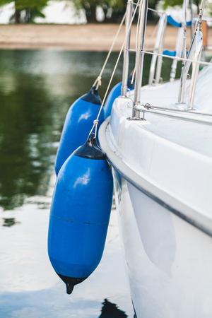 Several blue floats fenders hang on the white board the yacht