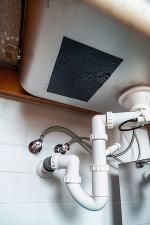 Rectangular stainless kitchen sink and drainage system of plastic pipes. bottom view Stock Photo