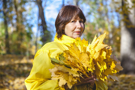 Elderly attractive woman hiding her face behind armful yellow autumn leaves in forest on sunny afternoon Stock Photo