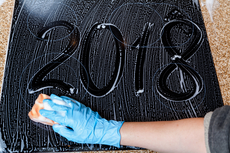 New Year in the kitchen. The numbers for the new year 2018 are written on a dark surface covered with soap foam. Bottom hand in a rubber glove