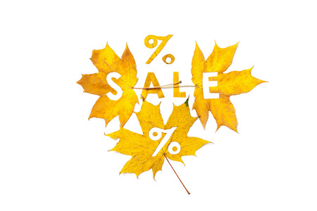 Discounts in the autumn period. Letters percent sign carved on a beautiful yellow maple leaf on a white background closeup