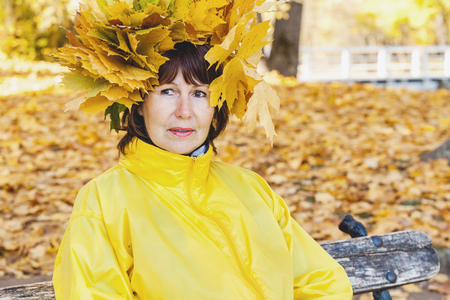 Cute elderly woman with a wreath of leaves on her head holding a large yellow maple leaves Stock Photo