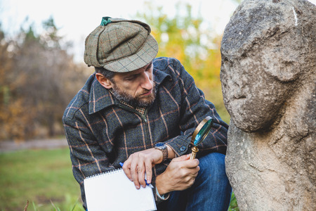 Scientists with a beard in a plaid jacket examines through a magnifying glass stone monument Scythian epoch on a green hillside