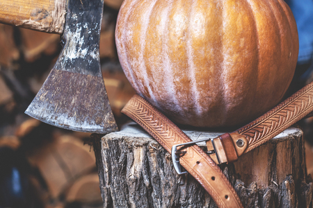 Autumn Still Life. Big ripe pumpkin lies on a stump beside the ax, leather belt close up