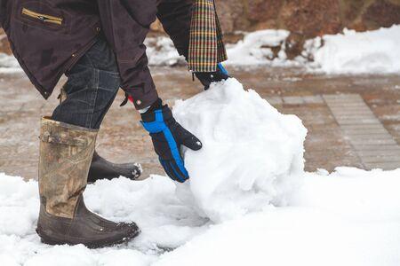 Handen in de skihandschoenen creëert een sneeuwbal winterdag