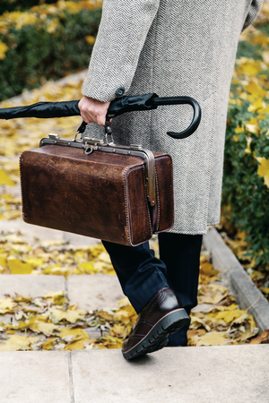 Gentleman style. A man in stylish shoes and a white coat walks the steps of the autumn park. An umbrella and a bag Stockfoto