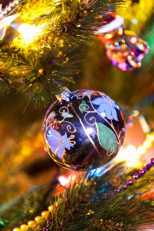 Bowl with flower pattern weighs on green fir branch closeup. Around blurry lights and garland
