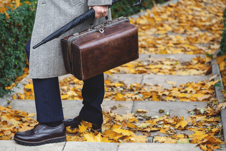 fallen tree: gentleman expects. A man in stylish shoes and a white coat is standing on the steps of an autumn park. An umbrella and a bag