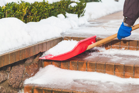 Man in rubber boots removes snow from the steps of the brick staircase with a large red plastic shovel