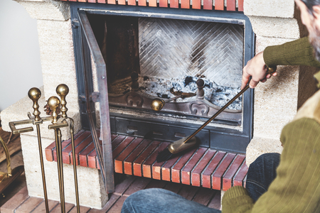 man cleans the furnace of fire with a spatula and brush on a long handle Reklamní fotografie - 89838604