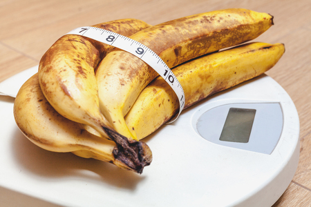 bunch of ripe bananas lay on plastic scales. Around the banana wrapped centimeter