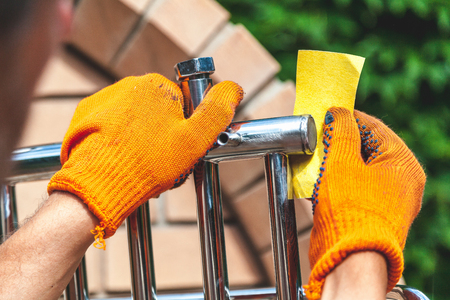 Grinding of a stainless heated towel rail. Hands in orange gloves clean out the metal structure with sandpaper