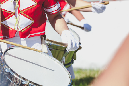 Several drummers girls in red uniforms playing on the circular cylindrical drums with wooden sticks
