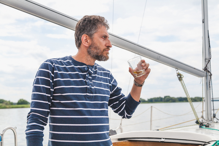 Businessman with a beard in a striped sweater drinks whiskey from a glass on a yacht close-up