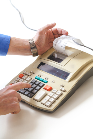 right hand presses the keys of the printing calculator, the left hand takes out a paper check