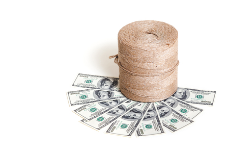 New roll flax cord standing on some banknotes on a white background