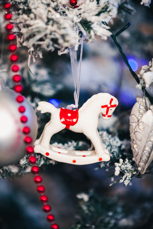 Original Christmas tree toy porcelain figurine of a horse weighs on a New Year tree. Around the red garland