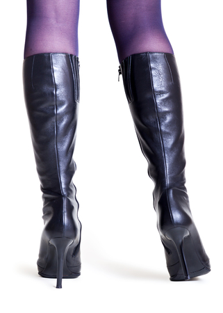 Slender female legs in fashionable high black leather boots on a thin heel on a white background. Back view
